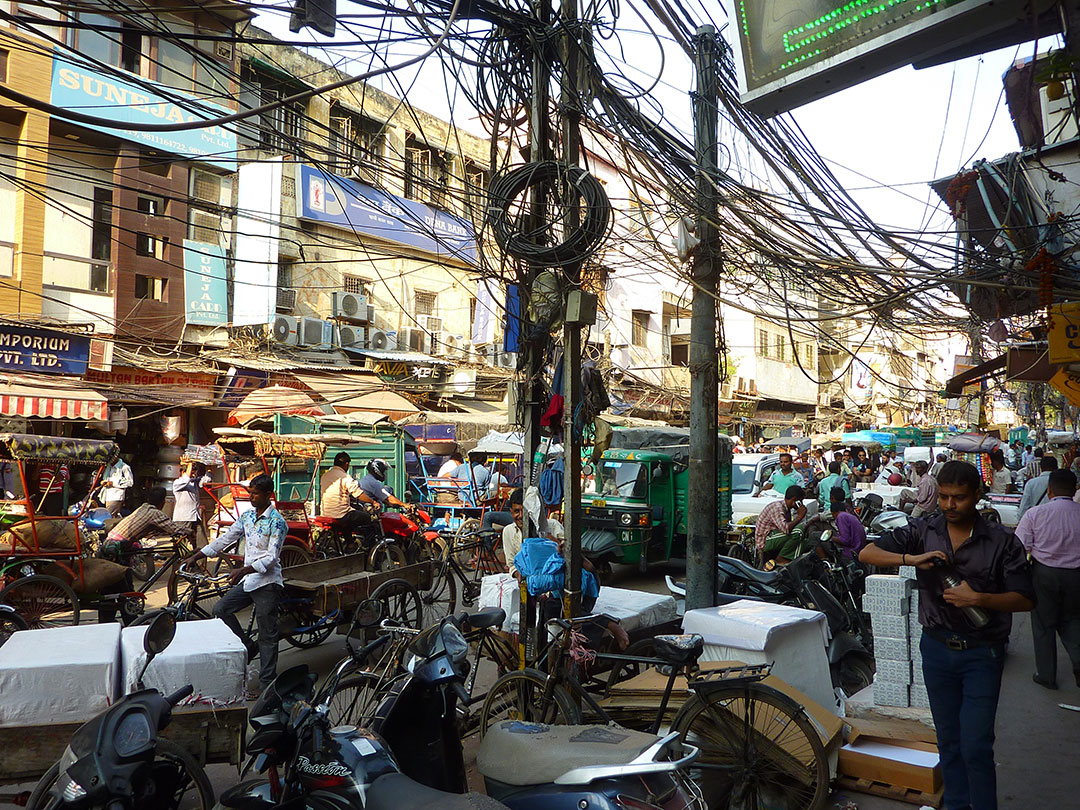 Tangled utility wires on a segment of a busy street in India.