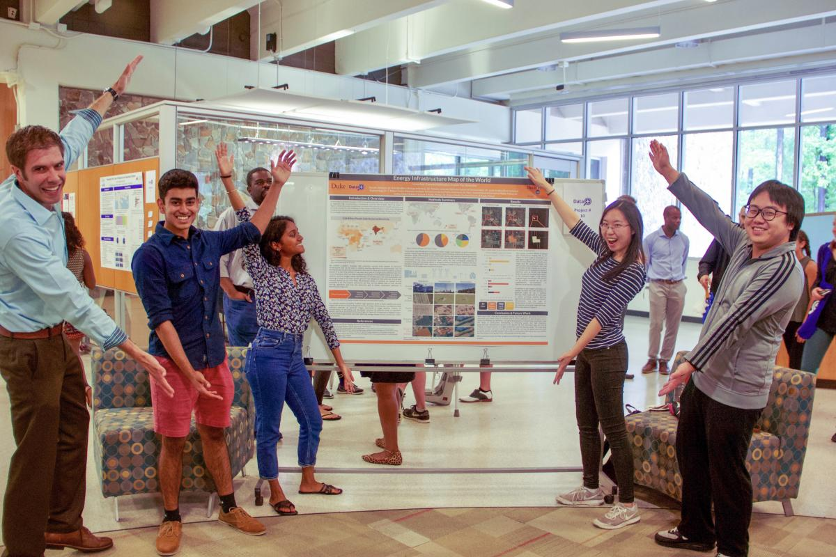 Students with Kyle Bradbury in front of their research poster