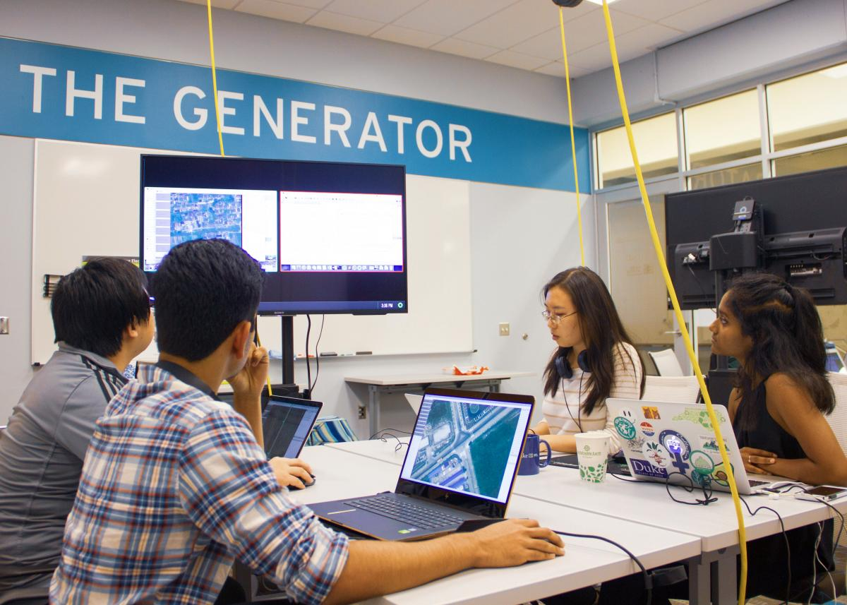 Students looking at computer screen in The Generator