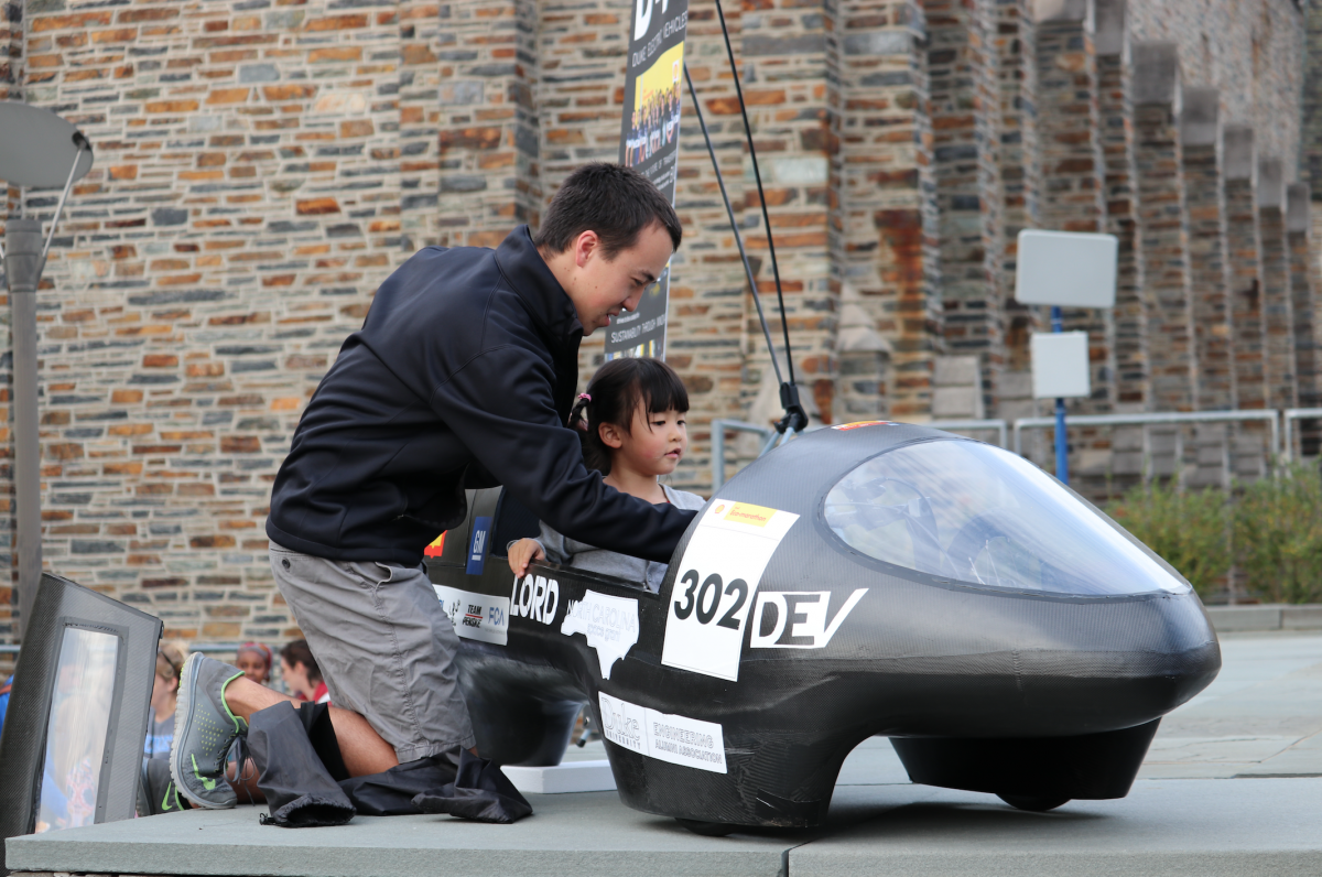 A Duke Electric Vehicles team member lets a little girl sit in the team's prototype vehicle