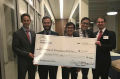 5 male students holding a giant check for $10K
